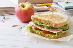 Πρόχειρο φαγητό για το σχολείο με το σάντουιτς, τη φρέσκια Apple και το χυμό από πορτοκάλι Ζωηρόχρωμες σχολικές προμήθειες Στοκ εικόνες με δικαίωμα ελεύθερης χρήσης