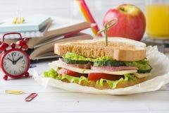 Πρόχειρο φαγητό για το σχολείο με το σάντουιτς, τη φρέσκια Apple και το χυμό από πορτοκάλι Ζωηρόχρωμες σχολικές προμήθειες Στοκ φωτογραφίες με δικαίωμα ελεύθερης χρήσης