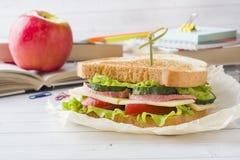 Πρόχειρο φαγητό για το σχολείο με το σάντουιτς, τη φρέσκια Apple και το χυμό από πορτοκάλι Ζωηρόχρωμες σχολικές προμήθειες Στοκ Φωτογραφία