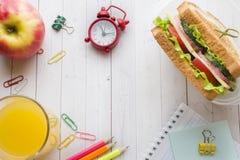 Πρόχειρο φαγητό για το σχολείο με το σάντουιτς, τη φρέσκια Apple και το χυμό από πορτοκάλι Ζωηρόχρωμες σχολικές προμήθειες διάστη Στοκ Φωτογραφίες