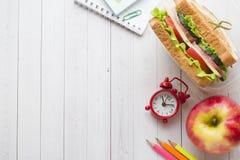 Πρόχειρο φαγητό για το σχολείο με το σάντουιτς, τη φρέσκια Apple και το χυμό από πορτοκάλι Ζωηρόχρωμες σχολικές προμήθειες διάστη Στοκ φωτογραφίες με δικαίωμα ελεύθερης χρήσης