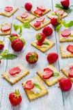 Πρόχειρο φαγητό: κροτίδες με το τυρί κρέμας, τις φρέσκα φράουλες και τα φύλλα μεντών στο ελαφρύ ξύλινο υπόβαθρο Στοκ εικόνα με δικαίωμα ελεύθερης χρήσης