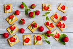 Πρόχειρο φαγητό: κροτίδες με το τυρί κρέμας, τις φρέσκα φράουλες και τα φύλλα μεντών στο ελαφρύ ξύλινο υπόβαθρο Στοκ φωτογραφία με δικαίωμα ελεύθερης χρήσης