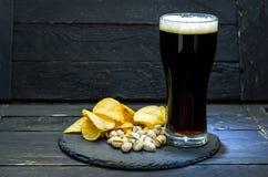 Πρόχειρο φαγητό μπύρας και ένα ποτήρι της μπύρας Μπύρα και αφρός Στοκ Εικόνες