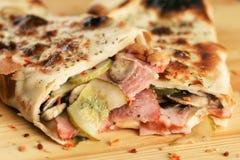 Πρόχειρο φαγητό σάντουιτς ρόλων πιτσών με την κινηματογράφηση σε πρώτο πλάνο ζαμπόν Στοκ Εικόνες