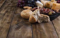 Πρόχειρο φαγητό στο κρασί Φρέσκο ψημένο ψωμί Διαφορετικό πρόχειρο φαγητό για το κρασί Τυρί, ελιές, διάστημα αντιγράφων σταφυλιών Στοκ Εικόνα