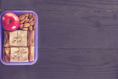 Πρόχειρο φαγητό στο σχολείο, πρόχειρο φαγητό για να εργαστεί, μεσημεριανό γεύμα με σας, πίτα μήλο και καρύδια σε ένα εμπορευματοκ Στοκ Φωτογραφία