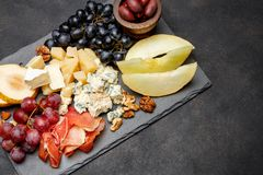 Πρόχειρο φαγητό antipasti πιάτων κρέατος - ζαμπόν Prosciutto, μπλε τυρί, πεπόνι, σταφύλια, ελιές Στοκ εικόνα με δικαίωμα ελεύθερης χρήσης