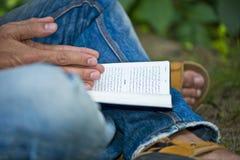 Πρώην-μουσουλμανική Βίβλος ανάγνωσης νεαρών άνδρων έξω Στοκ Εικόνες