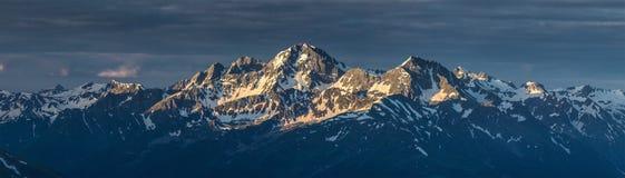 Πρώτες ακτίνες της αύξησης του ήλιου στην αιχμή βουνών που καλύπτεται από το χιόνι Στοκ Εικόνες