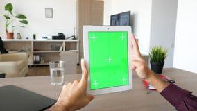 Πρώτη άποψη προσώπων των αρσενικών χεριών που κρατά ένα ψηφιακό PC ταμπλετών στα χέρια με την πράσινη χλεύη χρώματος οθόνης επάνω απόθεμα βίντεο