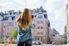 Πρώτη ημέρα στη νέα ευρωπαϊκή πόλη Όμορφη κυρία που παίρνει μια φωτογραφία ενός σπιτιού με τη ψηφιακή κάμερα Είναι ντυμένη στα πε στοκ φωτογραφία