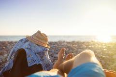 Πρώτη προοπτική προσώπων των ποδιών ατόμων στην παραλία ηλιοβασιλέματος Στοκ Εικόνα