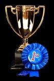 Πρώτο βραβείο θέσεων  χρυσό φλυτζάνι και μπλε κορδέλλα Στοκ φωτογραφία με δικαίωμα ελεύθερης χρήσης