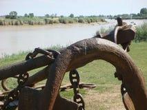 Πρώτο πλάνο μιας αρχαίας άγκυρας με έναν ποταμό πίσω σε Rochefort στη Γαλλία στοκ εικόνες