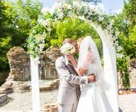 Πρώτο φιλί πρόσφατα του παντρεμένου ζευγαριού κάτω από τη γαμήλια αψίδα Στοκ Φωτογραφία