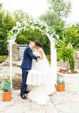 Πρώτο φιλί πρόσφατα του παντρεμένου ζευγαριού κάτω από τη γαμήλια αψίδα Στοκ φωτογραφία με δικαίωμα ελεύθερης χρήσης