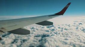 Πτήση αεροπλάνων Φτερό ενός αεροπλάνου που πετά επάνω από τα σύννεφα με τον ηλιόλουστο ουρανό απόθεμα βίντεο