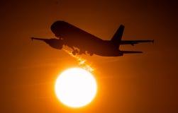 Πτήση αεροπλάνων στον ήλιο ηλιοβασιλέματος Στοκ Εικόνα