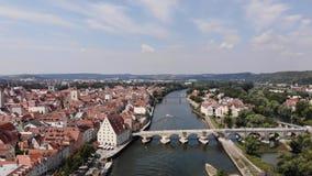 Πτήση πέρα από τον ποταμό Δούναβη, κατ' ευθείαν μπροστά μια πέτρινη γέφυρα και γέφυρα των εραστών, 4K Εναέρια άποψη του Ρέγκενσμπ απόθεμα βίντεο