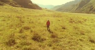 Πτήση πέρα από το περπάτημα τουριστών πεζοπορίας σακιδίων πλάτης πέρα από τον πράσινο τομέα βουνών r φιλμ μικρού μήκους