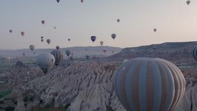 Πτήση πολλών ζωηρόχρωμη μπαλονιών ζεστού αέρα επάνω από τα βουνά - πανόραμα Cappadocia στην ανατολή απόθεμα βίντεο