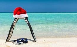 Πτερύγια και μάσκα με το καπέλο Χριστουγέννων σε μια τροπική παραλία στοκ εικόνα με δικαίωμα ελεύθερης χρήσης