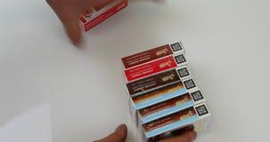 Πτυχές χεριών ατόμων στο συσκευάζοντας πίνακα με τον καπνό φιλμ μικρού μήκους