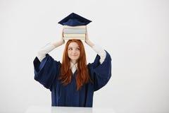 Πτυχιούχος κοριτσιών πιπεροριζών στα βιβλία εκμετάλλευσης χαμόγελου μανδυών στο κεφάλι κάτω από την ΚΑΠ πέρα από το άσπρο υπόβαθρ Στοκ Εικόνες