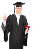 Πτυχιούχος κολλεγίου που δίνει έναν αντίχειρα επάνω Στοκ Εικόνες