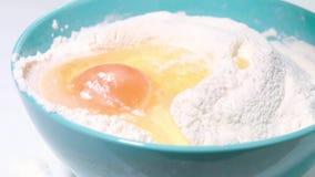 Πτώσεις αυγών στο σε αργή κίνηση πυροβολισμό αλευριού φιλμ μικρού μήκους