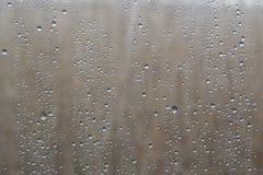 Πτώσεις βροχής κινηματογραφήσεων σε πρώτο πλάνο στο γυαλί με το φυσικό υπόβαθρο έξω από το παράθυρο Στοκ Εικόνα