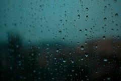 Πτώσεις βροχής σε ένα παράθυρο κρυστάλλου στο βράδυ με τα δέντρα και το υπόβαθρο ουρανού στοκ φωτογραφία
