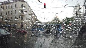 Πτώσεις βροχής σε ένα παράθυρο που αγνοεί έναν δρόμο με τη διάβαση των αυτοκινήτων απόθεμα βίντεο