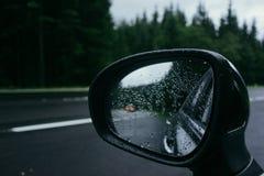 Πτώσεις βροχής στον καθρέφτη πλάγιας όψης αυτοκινήτων Στοκ Φωτογραφία