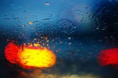 Πτώσεις βροχής στο γυαλί αυτοκινήτων με το φωτεινό σηματοδότη, εστίαση στις σταγόνες βροχής Στοκ Φωτογραφίες