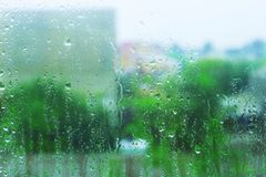 Πτώσεις βροχής στο διαφανές γυαλί παραθύρων ενάντια στα πράσινα δέντρα και την οικοδόμηση αφηρημένη ανασκόπηση ζωηρόχρωμη Στοκ Φωτογραφίες