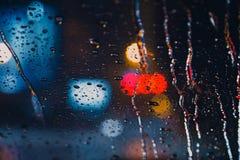 Πτώσεις βροχής στο παράθυρο με βρέχοντας εποχή οδικού την ελαφριά bokeh Στοκ Εικόνες