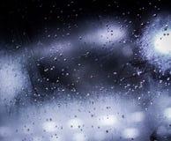 Πτώσεις βροχής στο παράθυρο με τα φω'τα bokeh Στοκ εικόνα με δικαίωμα ελεύθερης χρήσης