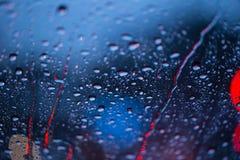 Πτώσεις βροχής στο παράθυρο με το οδικό φως bokeh, περίοδος βροχών Στοκ Φωτογραφία