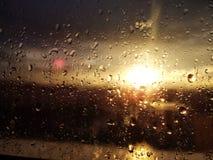 Πτώσεις βροχής στο παράθυρο με το σύνολο ήλιων Στοκ Φωτογραφίες