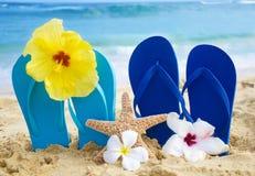 Πτώσεις και αστερίας κτυπήματος με τα τροπικά λουλούδια στην αμμώδη παραλία Στοκ Φωτογραφίες