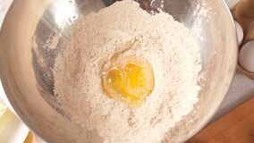 Πτώσεις λέκιθου αυγών σε ένα κύπελλο γυαλιού με το αλεύρι φιλμ μικρού μήκους