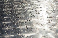 Πτώσεις νερού σε μια λαμπρή επιφάνεια μετάλλων Υπόβαθρο Στοκ εικόνα με δικαίωμα ελεύθερης χρήσης