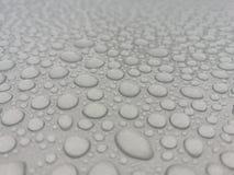 Πτώσεις νερού στην γκρίζα ταπετσαρία στοκ φωτογραφίες