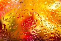 Πτώσεις νερού στο γυαλί με το ζωηρόχρωμο υπόβαθρο Στοκ εικόνα με δικαίωμα ελεύθερης χρήσης