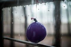 Πτώσεις στο κιγκλίδωμα μπαλονιών και μετάλλων παιδιών, θερινή βροχή Στοκ Εικόνες