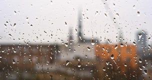 Πτώσεις της βροχής σε ένα παράθυρο, κτήρια στο υπόβαθρο απόθεμα βίντεο