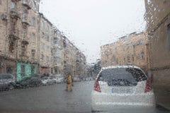 Πτώσεις της βροχής στον ανεμοφράκτη αυτοκινήτων, υπόβαθρο γυαλιού, να εξισώσει Φω'τα Bokeh οδών από την εστίαση στοκ εικόνες με δικαίωμα ελεύθερης χρήσης
