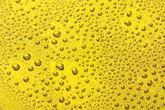 Πτώσεις του νερού σε ένα υπόβαθρο χρώματος κίτρινος Στοκ εικόνες με δικαίωμα ελεύθερης χρήσης